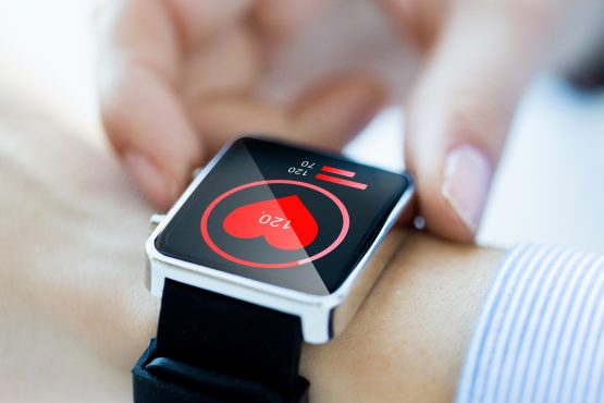 close up of hands with heart icon on smartwatch